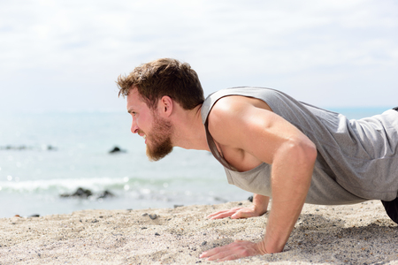 planking: Fitness man doing push-up exercise on beach. Portrait of fit guy working out his arm muscles and body core with pushup exercises on sand beach.