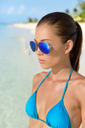 woman  glasses: Beach bikini Asian woman wearing fashion eye wear. Young female adult model with trendy blue mirrored aviator mirror sunglasses and turquoise swimwear top looking at the ocean. Stock Photo
