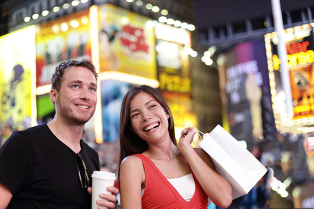 Happy couple shopping fun on New York city travel. Two tourists multiracial group enjoying night on Time Square, USA drinking coffee and walking with shopping bags during summer. American lifestyle. Stock Photo
