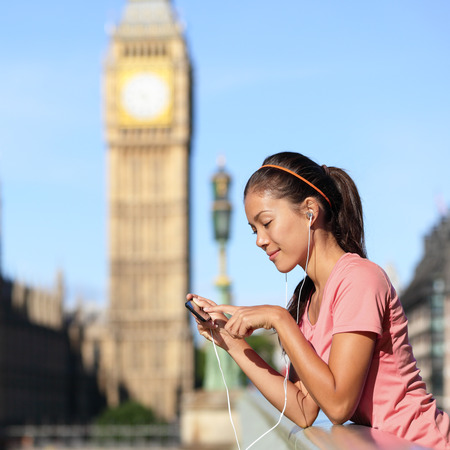London fitness lifestyle woman listening to running music playlist on smartphone. Female resting after training in urban city street. Runner girl near Big Ben, Westminster Bridge, London, England, UK