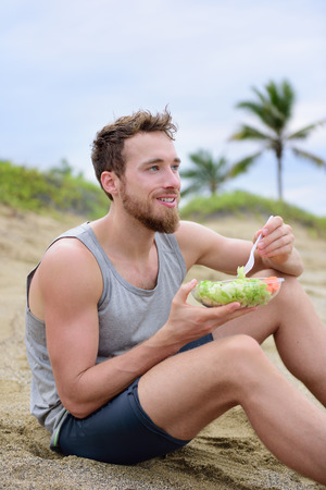 lunch meal: Fitness man eating healthy salad meal at workout. Handsome young muscular male adult sitting on the beach after running workout for lunch break with fresh prepared to go vegan raw vegetables food. Stock Photo