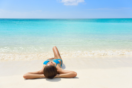 bathing women: Tropical Caribbean beach vacation - suntan relaxation woman. Bikini girl lying down relaxing on white sand exotic destination sleeping and sunbathing during summer holidays. Stock Photo