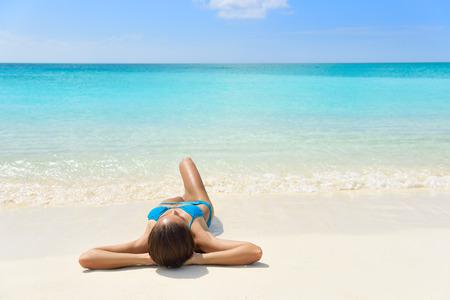 personas banandose: Vacaciones tropicales de la playa del Caribe - Relajación de la mujer del bronceado. chica del bikini relajante acostado en la arena blanca de dormir destino exótico y tomar el sol durante las vacaciones de verano.
