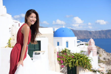 mediterranea: Santorini Thira Greece island tourism - Asian woman wearing red dress on summer travel looking at view with the famous attraction three domes chapel church in the background. Luxury destination. Stock Photo