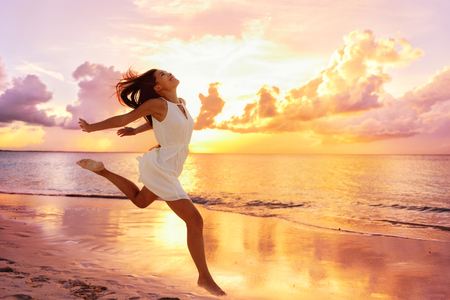 bliss: Freedom wellness well-being happiness concept. Happy carefree Asian woman feeling blissful jumping of joy on peaceful beach at sunset. Serenity, relaxation, mindfulness, stress free concepts. Stock Photo