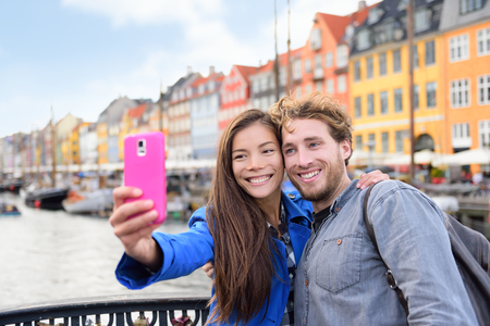 scandinavian people: Copenhagen travel people taking friends selfie picture photos as souvenir with smartphone camera. Couple of tourists in the old port Nyhavn, famous Scandinavian attraction in Denmark, northern Europe. Stock Photo