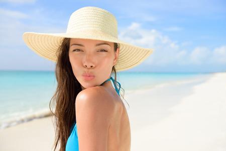 Plage chapeau de soleil femme soufflant joli baiser en vacances. modèle jeune femme asiatique adulte frappant un baiser pose à la caméra pour les vacances d'été portant la paille sunhat et bikini bleu sur le sable blanc parfait. Banque d'images - 53759015