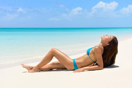 personas banandose: Mujer del bronceado bikini relajante en vacaciones en la playa para tomar el sol bronceado  sol en perfecta playa de arena blanca de color turquesa para las vacaciones de verano. Modelo asiático con cuerpo sexy y trajes de baño azul para el concepto de pérdida de peso.