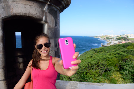 san juans: Tourist taking fun selfie at famous landmark. Travel woman holding a pink smartphone visiting Old San Juans Castillo San Felipe Del Morro, the main attraction of the city of San Juan, Puerto Rico. Stock Photo