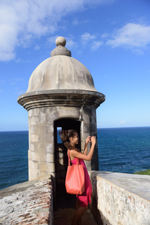 juan: Puerto Rico woman taking pictures with smartphone at Old San Juan Fort Castillo San Felipe Del Morro. Asian tourist on her american travel visiting a famous landmark during summer vacations.