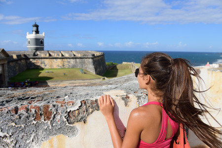 spanish culture: Puerto Rico travel tourist woman in San Juan, looking down at the fort Castillo San Felipe Del Morro, famous attraction of Old San Juan city in Puerto Rico, USA. Summer holidays.