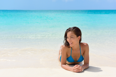 girl lying down: Beach vacation woman relaxing on sand happy. Asian mixed race model looking happy lying down on perfect white sand beach and turquoise ocean water for luxury summer vacations in exotic destination.