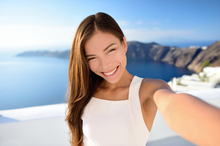 Asian beauty selfie woman on Santorini summer travel. Beautiful young adult mixed race Chinese Caucasian female model taking picture with smartphone smiling at camera. Skincare makeup concept. Фото со стока - 53759085