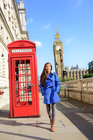 phonebooth: London tourism. Asian tourist woman walking by famous touristic attraction red phone booth or telephone box with Big Ben Westminster bridge in the background. Early spring or fall autumn travel.