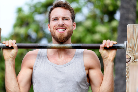 strong chin: Crossfit fitness man exercising chin-ups workout. Young male adult trainer athlete portrait closeup with hands holding on monkey bars at outdoor gym doing a chin-up strength training muscle exercise. Stock Photo