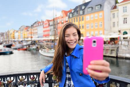 コペンハーゲンのニューハウンで selfie を取ってアジア観光女性。有名なランドマーク、北ヨーロッパの目的地、北欧、デンマークのコペンハーゲン