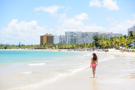 spanish girl: People on Isla Verde resort beach in Puerto Rico. Unrecognizable woman walking down the beach on summer holiday in bikini on famous Hispanic travel destination.