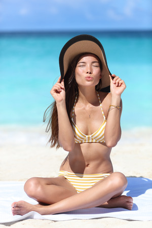 Cute suntan woman tanning blowing kiss on beach vacation wearing straw hat for sun protection tanning during summer holidays wearing fashion golden stripes retro bikini outfit.