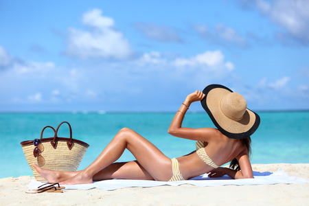 girl with towel: Sexy bikini woman tanning relaxing on beach. Suntan concept. Unrecognizable female adult from the back lying down with straw hat sunbathing under the tropical sun on Caribbean vacation.