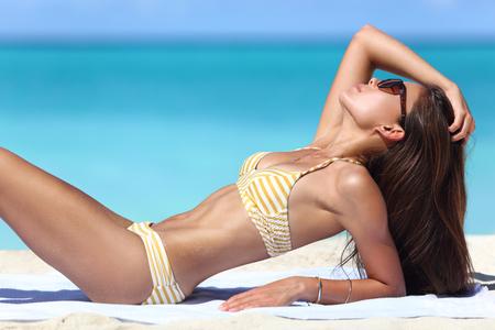 Sexy Sonnenstrand Frau in Mode Bikini Sonnenbaden. Schöne fit Körper der Modell entspannenden Bräunungs auf Handtuch. Gewichtsverlust oder Sonnenschutz-Konzept der Hautpflege.