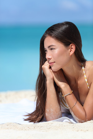 sun care: Asian beauty woman relaxing on beach during summer vacation travel. Face closeup of Chinese Caucasian mixed race fashion model posing with bracelets and sun care makeup for skincare concept. Stock Photo