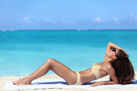 Suntan woman lying down relaxing getting a bikini sun tan on Caribbean beach summer vacation travel destination. Sexy Asian woman with slim body for weight loss concept. Stock Photo