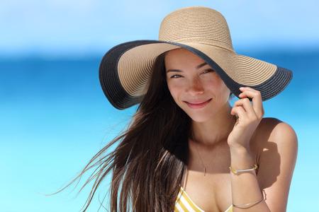 proteccion: La mujer asiática con el sombrero de paja de la playa de la moda para protegerse del sol cuidado de la piel. Enfrentar el concepto de belleza cuidado de la piel. joven de raza mixta retrato adulto de raza caucásica china hermosa chica en los viajes de vacaciones de verano. Foto de archivo