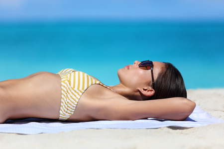 sun care: Beach sunglasses woman tanning relaxing in bikini. Sexy young adult wearing eyewear for sun protection lying down on towel on sand sunbathing closeup portrait. Skincare UV sun care concept. Stock Photo
