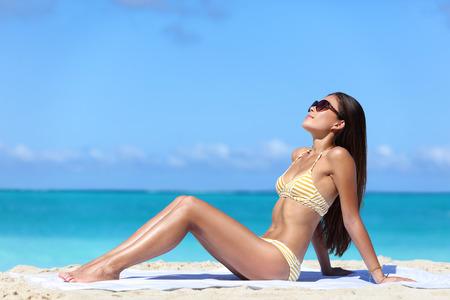 personas banandose: Gafas de sol de la playa tomar el sol Mujer en bikini atractivo. chica de cuerpo completo que se acuesta conseguir un bronceado en la piel que llevaba gafas. Cuidado de la piel concepto de protección contra los rayos UV solares.