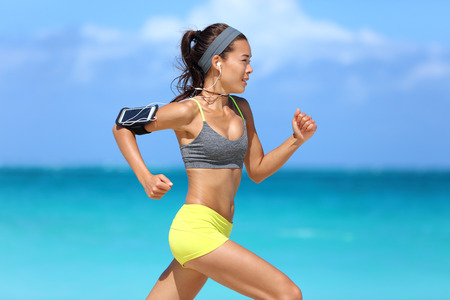 Athlete running woman runner listening to music on her phone sports armband with touchscreen and headphones earphones on summer beach. Fitness girl jogging fast training cardio and glutes.