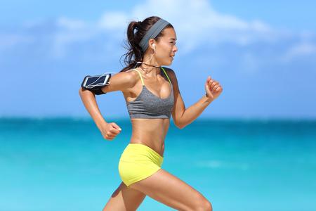 motion: Idrottsman som kör kvinna löpare som lyssnar på musik på hennes telefon sportband med pekskärm och hörlurar hörlurar på sommarstranden. Fitness tjej joggar snabbt träning cardio och glutes.