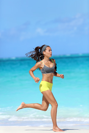 Active, healthy and fit lifestyle - woman running barefoot on beach. Asian female runner jogging full length on sand training her leg muscles and cardio on ocean background. Stock Photo