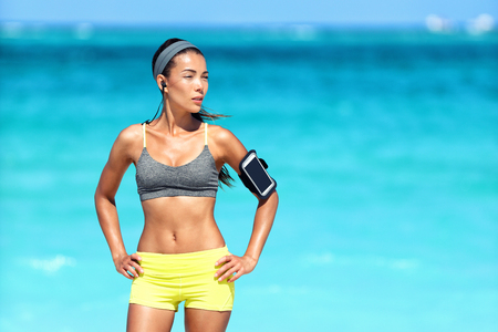 Asian fitness woman with sports bra and armband. Young female runner getting ready for strength training or cardio workout on beach in summer with ocean background. Fit active lifestyle.