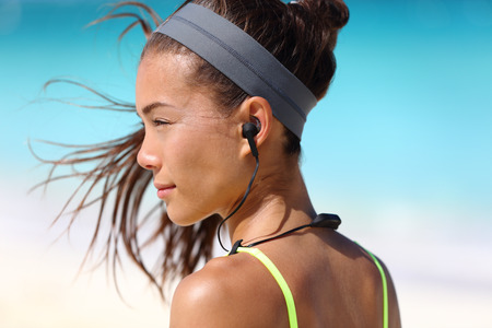 telephone headsets: Fitness girl with sport in-ear wireless headphones. Asian female athlete woman runner wearing Bluetooth earphones with wing tip design for sports activities. Portrait closeup. Stock Photo