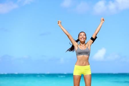 Gelukkig succes vrouw - bereiken van fitness doelen. Het winnen van vrouwelijke atleet met de armen omhoog succes van het bereiken van haar training of dieet doel. Gezonde Aziatische runner meisje het leven van een gezonde levensstijl.