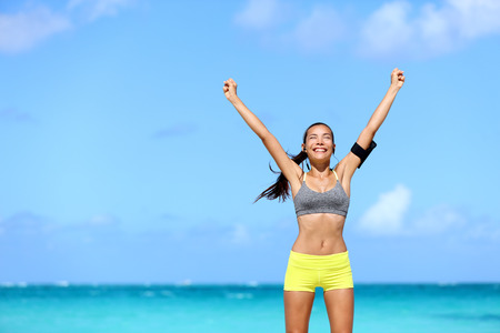 Happy success woman - achievement of fitness goals. Winning female athlete with arms up successful of achieving her workout or diet goal. Healthy Asian runner girl living a healthy lifestyle.