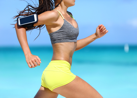 Fitness athlete woman running fast with speed wearing phone armband with touchscreen. Midsection crop showing muscular legs and thighs training glutes during intense cardio workout.