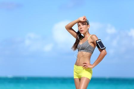 有酸素運動後汗疲れている女性ランナー。アジア実行中女性発汗ポストワーク頭痛原因頭の疲れや感動額を強打すること。熱中症・脱水症状概念。 写真素材