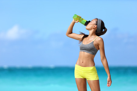 Fitness runner woman drinking water or energy drink of a sport bottle. Athlete girl taking a break during run to hydrate during hot summer exercise on beach. Healthy active lifestyle. Stock Photo