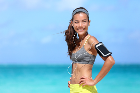 Happy fitness woman living a fit healthy lifestyle. Young Asian Caucasian girl wearing activewear and sports armband for phone and earphones, tech gear for running or cardio workout on beach.