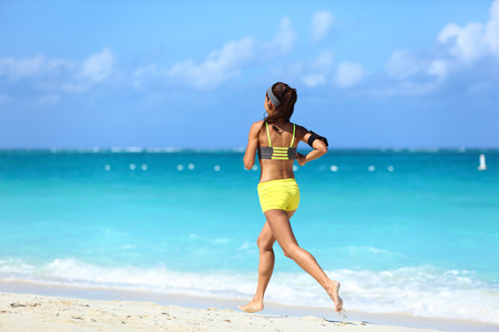 activewear: Running on beach - summer workout active lifestyle. Female athlete from the back running away barefoot on the sand in trendy activewear outfit training cardio for weight loss.
