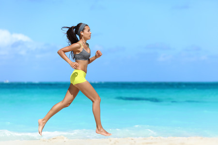 Fit female athlete girl runner running on beach. Full length body of woman jogging fast barefoot on sand training doing her cardio workout during summer vacation living a healthy lifestyle.