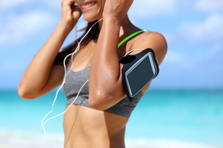estuches: Fitness phone armband runner woman putting earphones. Closeup of sports smartphone case holder touchscreen strap on female arm of person wearing headset for running exercise cardio workout on beach.