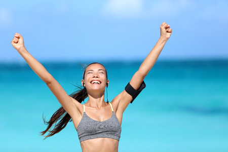 fitness goal: Happy running woman winning - fitness goal concept. Young Asian female runner smiling of happiness cheering with arms up wearing a sports bra, earphones and phone armband cheering of success.