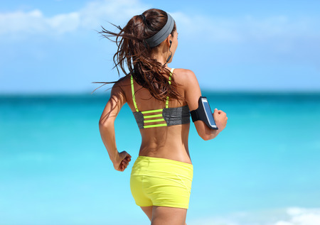 armband: Running motivation - runner training with music seen from behind jogging in fashion yellow straps sports bra and neon shorts outfit wearing wireless earphones on summer beach background.