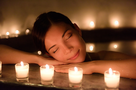 Beautiful young woman relaxing in hot tub at spa. Attractive female tourist is surrounded with lit candles. Smiling woman with eyes closed is pampering herself during vacation. 版權商用圖片