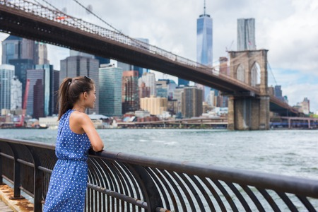 usa: New York city urban woman enjoying view of Brooklyn bridge and NYC skyline living a happy lifestyle walking during summer travel in USA. Female Asian tourist in her 20s.