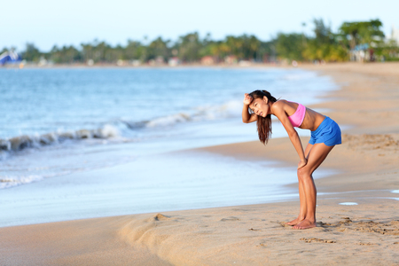 sunny beach: Exhausted runner relaxing on beach after running. Tired young woman is resting after jogging on sunny day. Full length side view of female in sportswear is looking away.