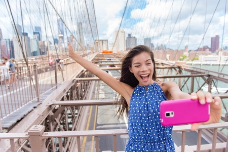 brige: Happy selfie tourist woman taking fun self-portrait picture with smart phone app on Brooklyn Brige, New York City, Manhattan, USA. Asian woman posing with smartphone for social media. Stock Photo