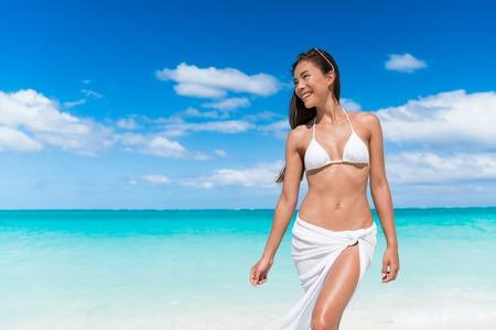 cintura: bikini mujer atractiva que se relaja en la playa con el estómago delgado que usa la tapa triángulo blanco y pareo que cubren hasta ropa de playa - concepto de pérdida de peso o la depilación. Foto de archivo